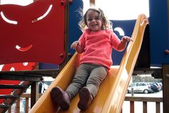 Little girl plays on a slide. Smiling little girl plays on a slide Stock Image