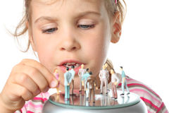 Little girl plays with small toy figures of people Royalty Free Stock Photos