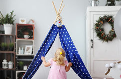 The little girl plays in a small wigwam