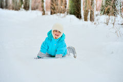Little girl plays with snow outdoors Royalty Free Stock Photography