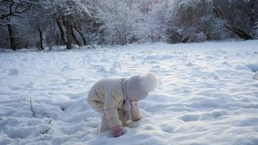 Little girl plays in snow stock video