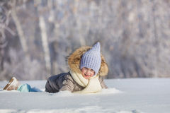 Little girl plays in snowdrift in winter Royalty Free Stock Photo
