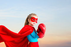 Little girl plays superhero on the background of sunset sky. Royalty Free Stock Image