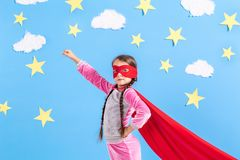 Little child plays superhero. Kid on the background of bright blue wall. Royalty Free Stock Photo
