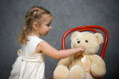 Little girl plays with teddy bear. Little girl plays with toy Royalty Free Stock Image