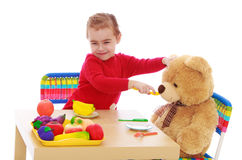 Little girl plays with a teddy bear Royalty Free Stock Photography