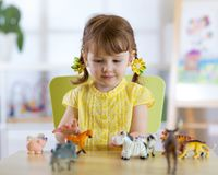 Little girl plays with little toy animals while sitting at table stock photo