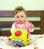 Little girl plays a toy baby on the bed Stock Images