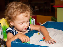 Little girl plays in sand. The little girl plays toys in sand Stock Photo