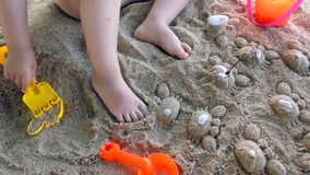 Little girl plays with toys in sand stock video footage