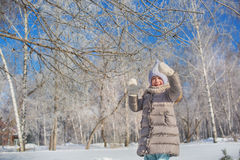 Little girl plays with tree in winter park in sunny day Royalty Free Stock Image
