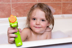 Little girl plays with water pistol in bath with foam Stock Images