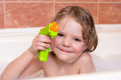 Little girl plays with water pistol in bath with foam Stock Photography