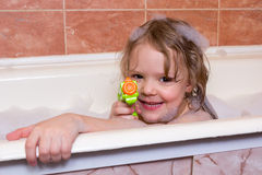 Little girl plays with water pistol in bath with foam. Little girl plays with water pistol in a bath with foam Royalty Free Stock Photography