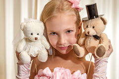 Little girl plays with wedding teddy-bear Stock Photos