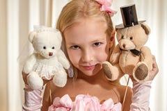 Little girl plays with wedding teddy-bear Stock Photos