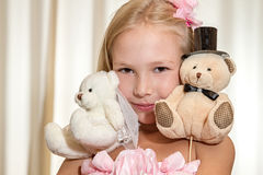 Little girl plays with wedding teddy-bear Stock Image