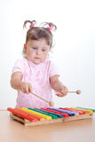 Little girl plays on xylophone. Charming toddler plays on xylophone Stock Photos