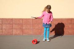 Little girl plays with yo-yo. Beautiful little girl plays with yo-yo on sunny day outdoor Stock Photography