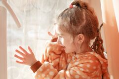 A little girl in plush pajamas with a hood plays on the window behind the curtain.