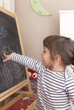 Little girl point at her drawing of flowers on blackboard Stock Photo