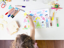 Little girl point at a sun in a kids drawing of multi-racial Fam Stock Image