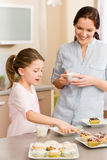 Little girl pointing cupcake to her mother Stock Photos