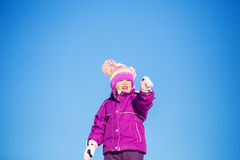 Little girl pointing into the distance. A four year old girl upper body wearing purple winter coat, mitts and snow hat squinting into the distance pointing with Stock Photo