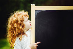 Little girl pointing finger at blackboard. Educational concept. Stock Images