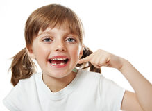 Little girl pointing her missing teeth. White background Stock Photos