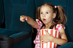 Little girl pointing to screen during film Stock Photography