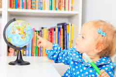 Little girl pointing to world globe in classroom. Early education Royalty Free Stock Photos