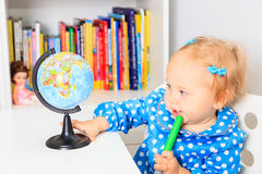 Little girl pointing to world globe in classroom, early education. Cute little girl pointing to world globe in classroom, early education Royalty Free Stock Images