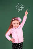 Little girl pointing upward in the studio Royalty Free Stock Photography