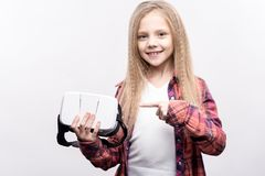 Little girl pointing at virtual reality headset in her hands. Modern technologies. Pleasant little girl in a checked shirt pointing at a virtual reality headset Royalty Free Stock Photos