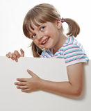 Little girl pointing on white blank Royalty Free Stock Image