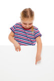Little girl pointing at whiteboard. Stock Photo