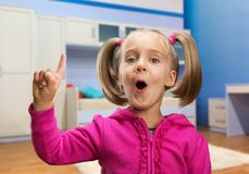 Little girl points her finger up Stock Images