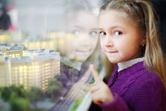 Little girl points at layout of residential buildings. Stock Photos