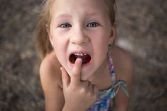 Free Little Girl Points The Finger At A Wobbly Baby Tooth Royalty Free Stock Images - 136071179
