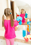 Little girl polishing mirror at bathroom with cleanser Stock Photography