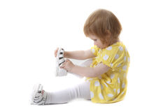 Little girl in polka dot dress and her shoe Royalty Free Stock Photography