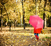 Little girl with polka dots umbrella walking through alley Stock Photo