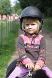 Little girl on pony. Close up of a little 4 year old girl sitting on a pony with a riding helmet Stock Photography