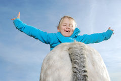 Little girl with pony. Portrait of a little happy girl lying on  a pony Royalty Free Stock Photos