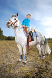 Little girl with pony. Portrait of a little happy girl riding a pony Stock Photography