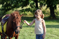 Little girl and pony horse pet on field Stock Photo