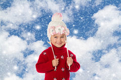 Little girl with ponytails in a warm hat and red sweater Royalty Free Stock Image