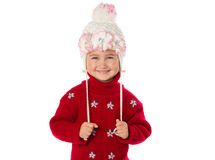 Little girl with ponytails in a warm hat and red sweater  on a w Royalty Free Stock Photography