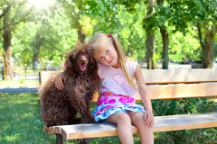 Little girl and poodle dog. Little girl hugging a poodle dog in the park royalty free stock photography
